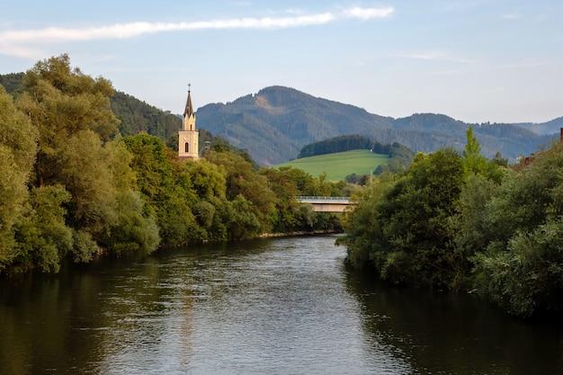 Vista del fiume della mur con la chiesa a leoben, austria Foto Premium