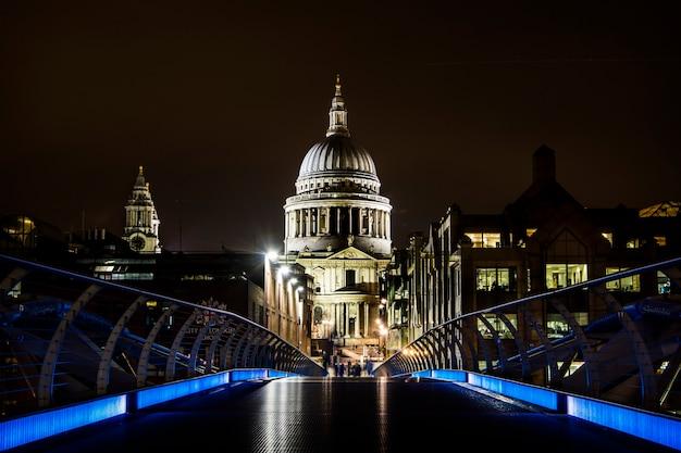 Vista della cattedrale di saint paul dalle luci blu del millenium bridge di notte a londra Foto Premium