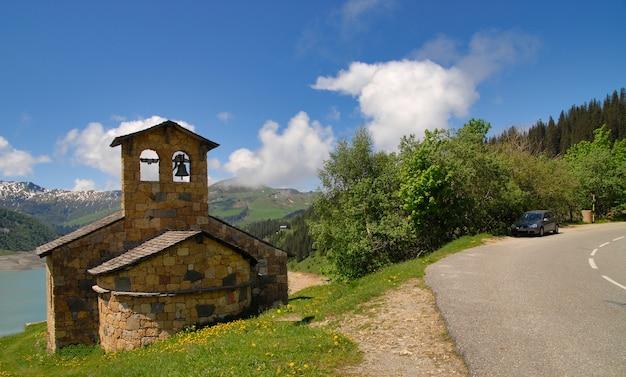 Vista della cappella di pietra sul lago roselend francia Foto Premium