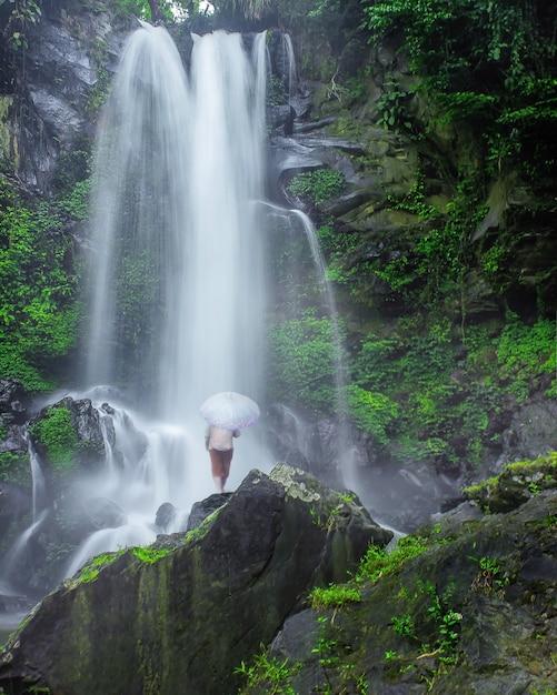 La vista di una cascata con una persona in piedi sotto è veramente bella in indonesia Foto Premium