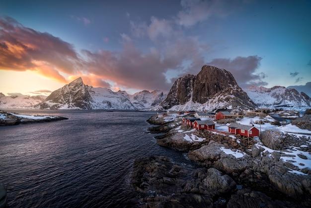 Villaggio con cabine rosse sul mare con le montagne sullo sfondo coperto di neve nel tramonto nelle isole lofoten, norvegia Foto Premium
