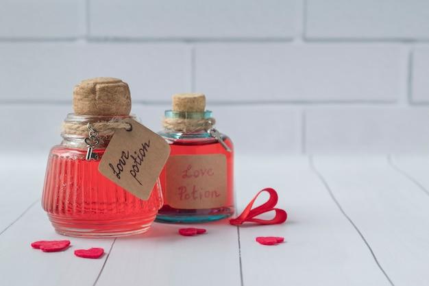 Bottiglie d'annata con pozioni d'amore magiche sulla tavola di legno bianca, spazio per testo Foto Premium