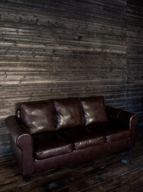 Sofà di cuoio marrone d'annata su una parete e su un pavimento di legno Foto Premium