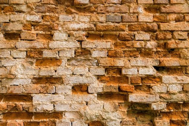 Muro di mattoni dell'argilla dell'annata di un edificio abbandonato Foto Premium