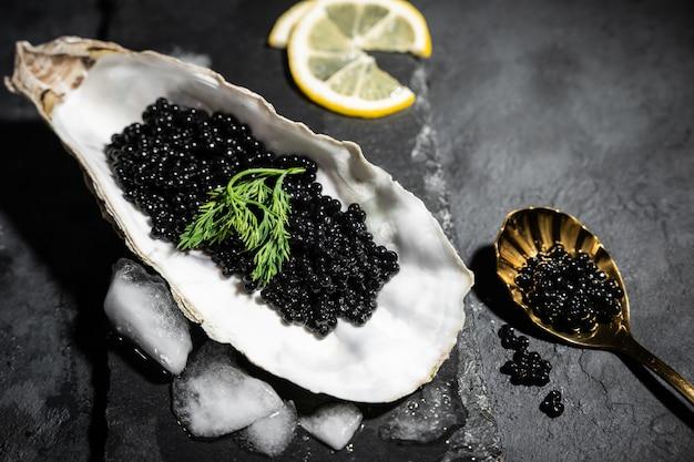Cucchiaio dorato d'annata con il caviale e l'ostrica neri dello storione sulla tavola di pietra nera dell'ardesia. copia spazio Foto Premium