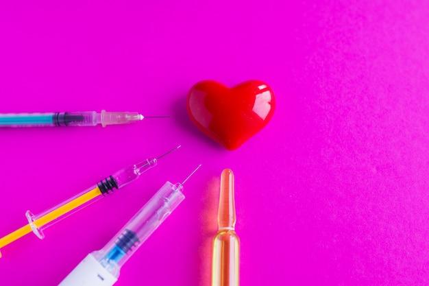 Cuore volumetrico con siringhe su uno sfondo rosa. il concetto di supportare i pazienti con malattie cardiache Foto Premium