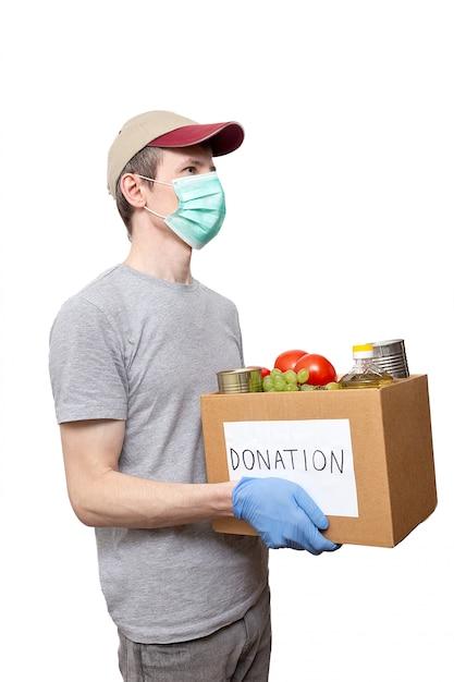 Volontario in guanti protettivi blu che mostrano l'alimento della drogheria in scatola di donazione del cartone Foto Premium