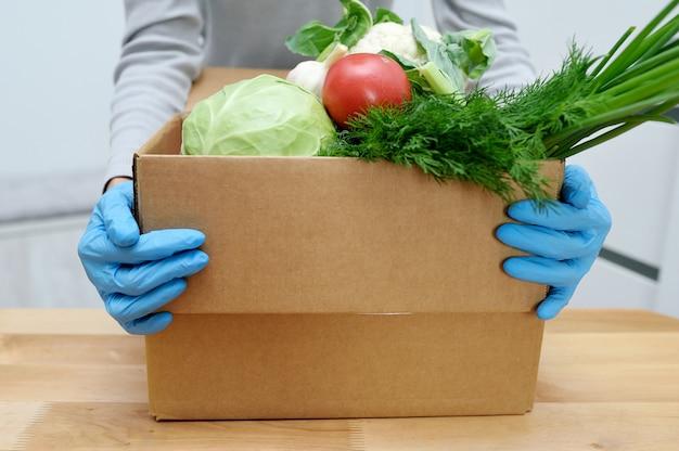 Il volontario in guanti tiene le verdure in scatola per donare cibo per aiutare i poveri. scatola di donat con prodotti alimentari Foto Premium