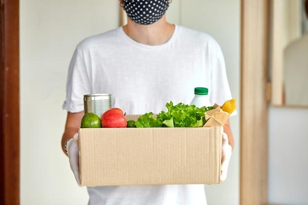 Volontario in maschera protettiva bianca e guanti consegna casella di donazione a casa Foto Premium