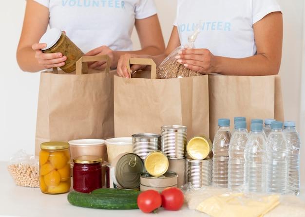 Volontari con sacchi di cibo e acqua da donare Foto Premium