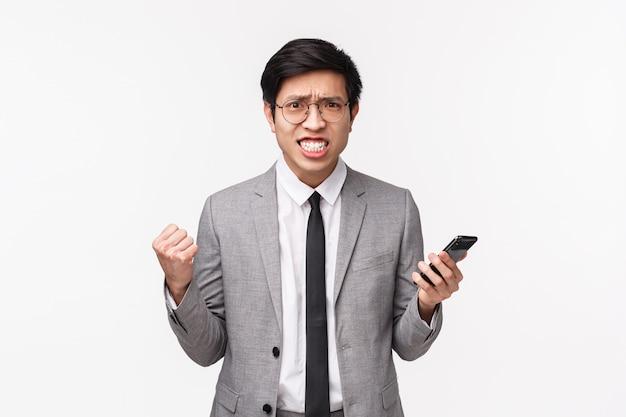 Mezzo busto di uomo d'affari asiatico scontento, infastidito e infastidito in abito grigio, stringendo denti e pugni, aggrottando le sopracciglia aggressivo, facendo smorfie irritato dalla lettura di cattive notizie sul cellulare Foto Premium