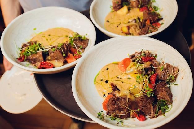 Il cameriere tiene in mano un piatto deliziose cotolette di carne succose, purè di patate cosparse di verdure e insalata fresca e sana di pomodori e foglie di lattuga Foto Premium