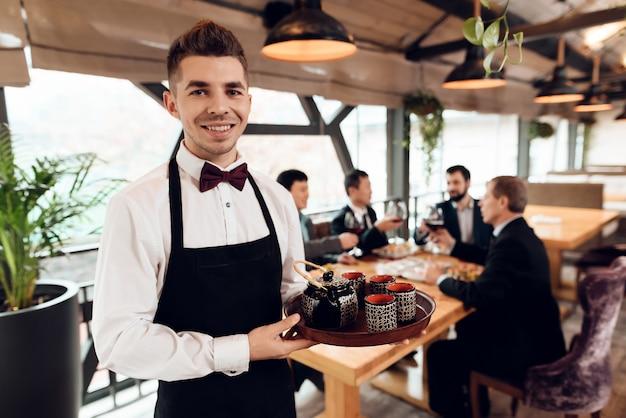Cameriere che prepara il tè per uomini d'affari asiatici Foto Premium