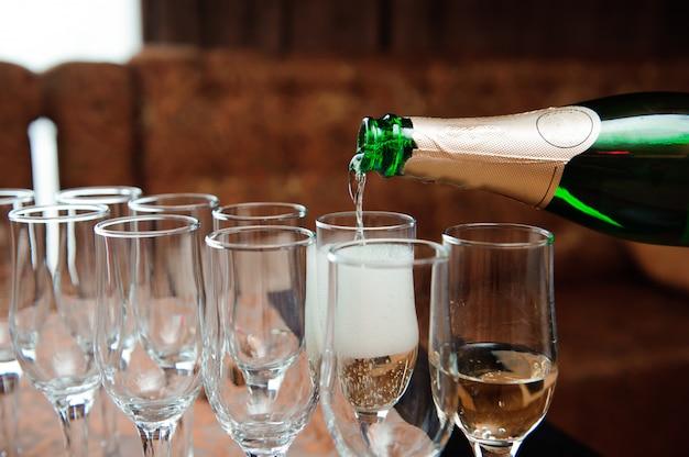 Cameriere versa champagne in bicchieri, evento di lusso. Foto Premium
