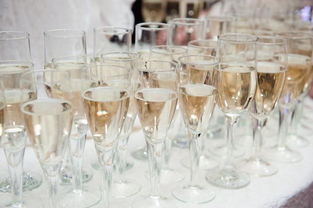 Cameriere versa champagne in bicchieri sul tavolo Foto Premium