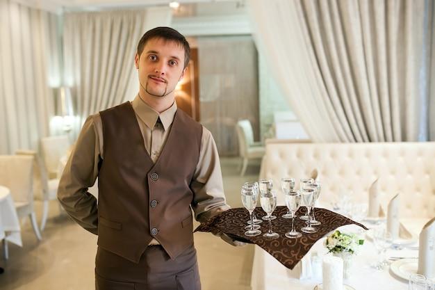 Il cameriere con un vassoio accoglie i visitatori Foto Premium