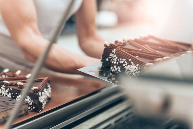 Cameriera organizzando la torta in vetrina Foto Premium