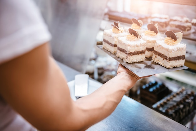 Cameriera che organizza torte Foto Premium