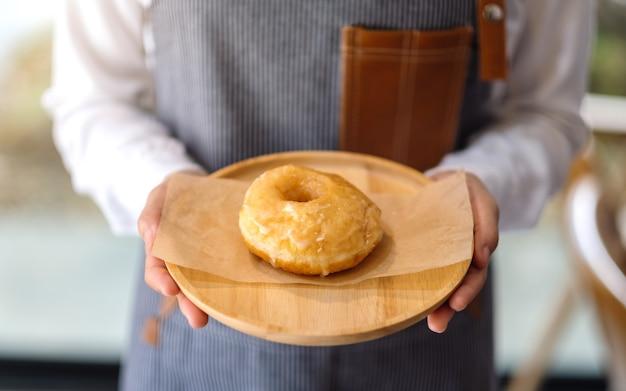 Una cameriera in possesso e servire un pezzo di ciambella fatta in casa nel vassoio di legno Foto Premium