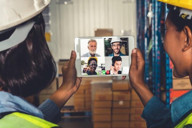 Il personale del magazzino parla in videochiamata allo schermo del computer nel magazzino di stoccaggio Foto Premium