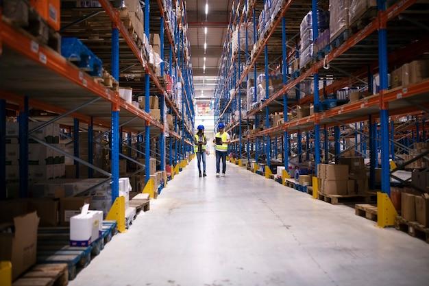 Magazzinieri che camminano nella grande area di stoccaggio della fabbrica. Foto Premium