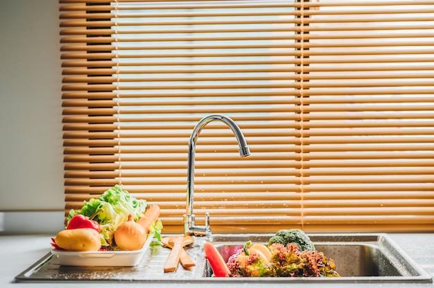 Lavare le verdure fresche nel lavandino con rubinetto Foto Premium