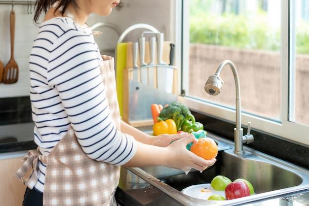 Lavare un'arancia e altri frutti sopra il lavello della cucina Foto Premium