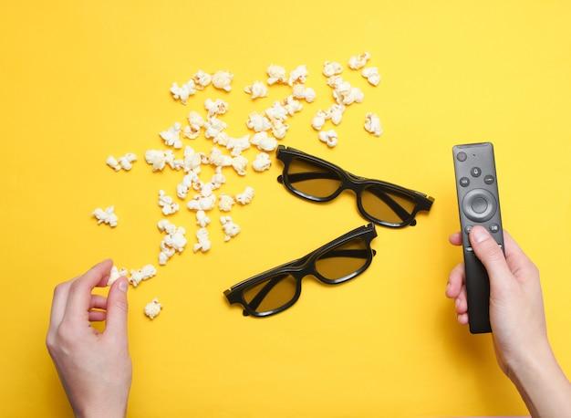 Guardare film. mani di stile piatto laici in possesso di telecomando tv, popcorn, due paia occhiali 3d su giallo. vista dall'alto. Foto Premium