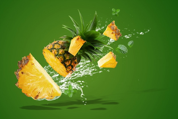 L'acqua che spruzza sull'ananas fresco è frutta tropicale isolata su verde Foto Premium