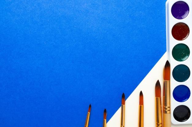 Scatola di pittura ad acquerello e set di pennelli su vista dall'alto di sfondo blu e bianco Foto Premium