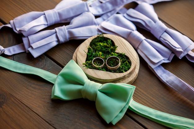 Fede nuziale in scatola a forma di cuore con muschio verde vicino a papillon per sposo e groomsmen Foto Premium