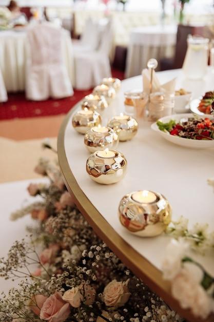 Tavola di nozze decorata con bellissime candele e colori diversi. cibo festivo sul tavolo. banchetto matrimoniale. Foto Premium