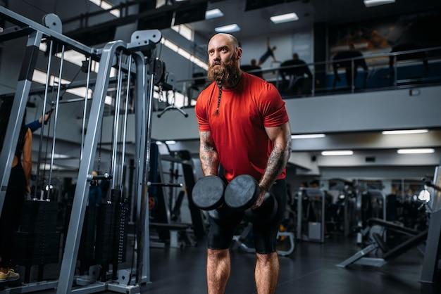 Sollevatore di pesi facendo esercizio con manubri in palestra Foto Premium