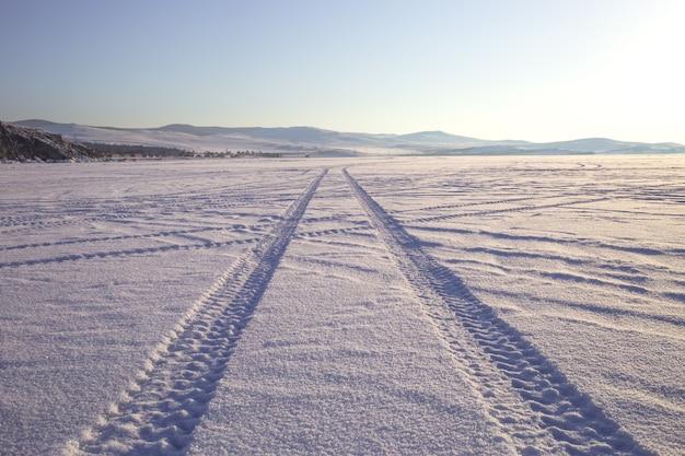 Tracce delle ruote sulla strada di inverno coperta di neve Foto Premium