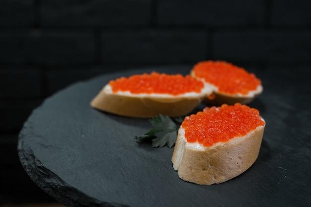 Snack baguette bianca con caviale rosso e burro con foglie di prezzemolo su un tavolo su uno sfondo nero in un ristorante. spuntino dietetico chic. ottima aggiunta alla cena. Foto Premium