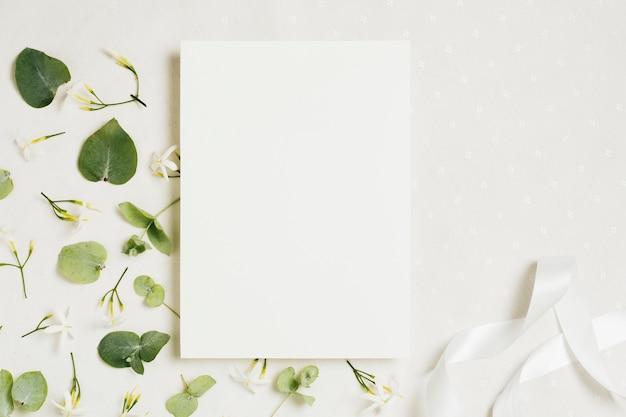 Partecipazione di nozze in bianco bianca con fiori e nastro jasminum auriculatum su sfondo bianco Foto Premium