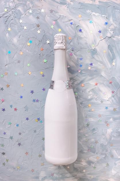Bottiglia di champagne bianco e coriandoli anno nuovo e concetto di celebrazione di natale Foto Premium