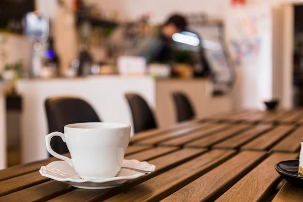 Tazza e piattino di caffè bianco sopra la tavola di legno nel bar Foto Premium