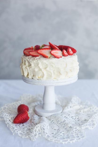 Torta crema bianca con la fragola sulla tabella bianca Foto Premium