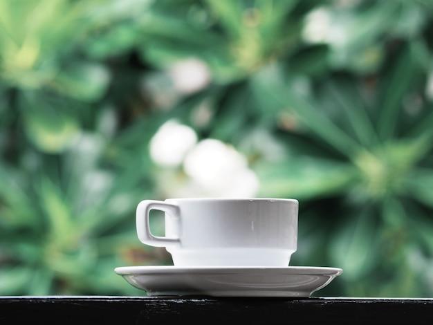 Tazza di caffè bianca sopra floreale verde. Foto Premium