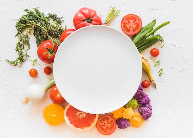 Cornice bianca vuota sopra le verdure colorate sullo sfondo Foto Premium