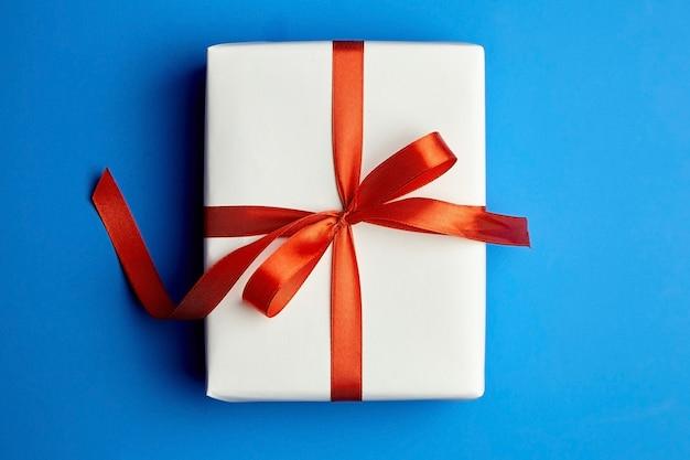Confezione regalo bianca legata con nastro rosso sull'azzurro Foto Premium