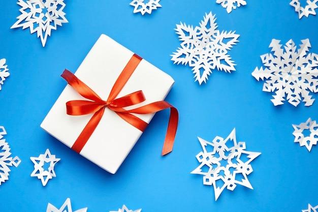 Scatola regalo bianca con nastro rosso e fiocchi di neve di carta sull'azzurro Foto Premium