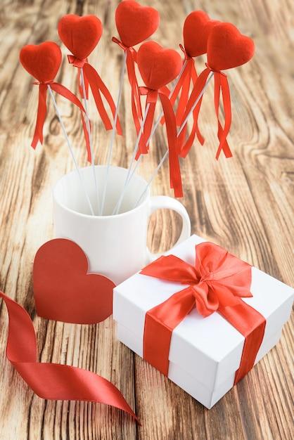 Contenitore di regalo bianco con fiocco in riibon rosso, tazza bianca con cuori rossi sul bastone, carta di cuore e fiori di rose dal nastro di raso su fondo di legno. Foto Premium