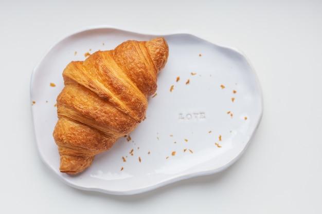 Piatto di argilla bianca fatta a mano con croissant freschi su un tavolo bianco Foto Premium
