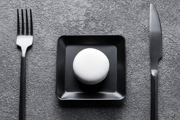 Torta di maccheroni bianchi in un piatto quadrato nero. bella composizione, minimalismo. Foto Premium