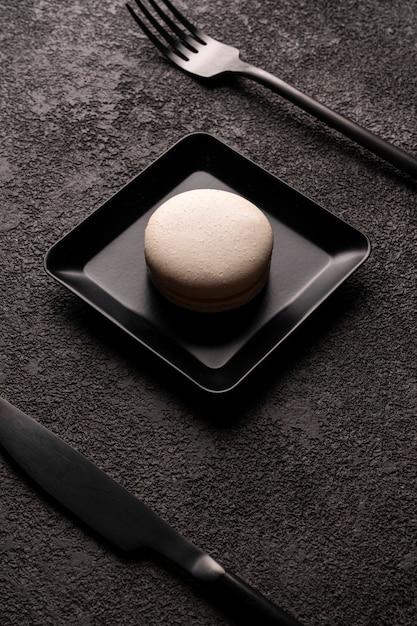 Torta amaretto bianco in un piatto quadrato. foto primo piano minimalista elegante. forchetta e cucchiaio neri. foto di cibo grafico in colori scuri, disposizione verticale. Foto Premium