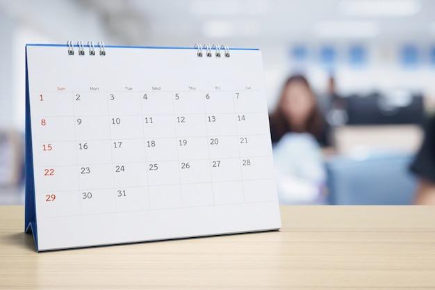 Calendario da tavolo in carta bianca sulla tavola di legno Foto Premium