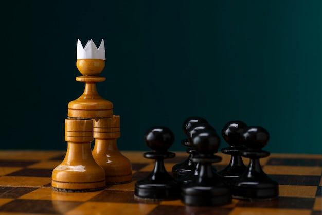 Pedone bianco con una corona di carta davanti a un esercito di pedoni neri Foto Premium