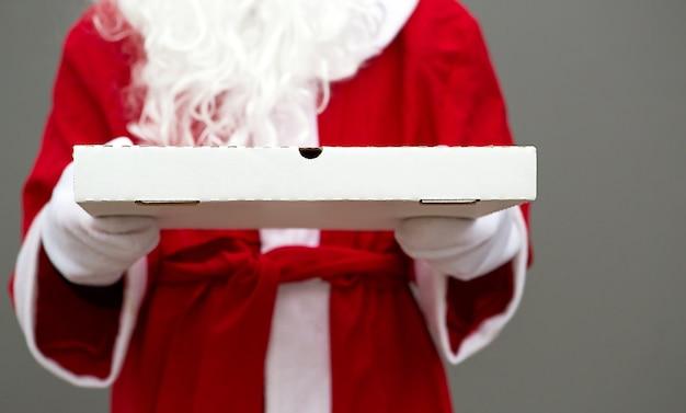 Scatola della pizza bianca nelle mani di babbo natale in guanti bianchi Foto Premium